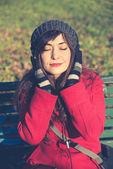 Beautiful woman red coat listening music — Stock Photo