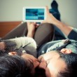 Stock Photo: Couple in love on bed using tablet