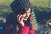 Beautiful woman red coat cellphone — Stock Photo
