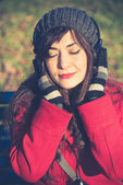 美しい女性の赤いコート音楽を聴く — ストック写真