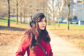 Beautiful woman red coat listening music — Stockfoto