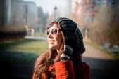 Beautiful woman red coat listening music — Stock Photo