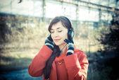 Beautiful woman red coat listening music park — Stock Photo