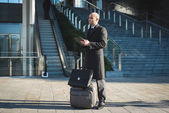 Successful elegant fashionable businessman using tablet — Stock Photo