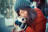 Beautiful woman red coat hugging the dog — Photo