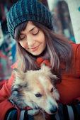 Beautiful woman red coat hugging the dog — Stock Photo