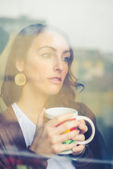 Beautiful woman with cup facing through window — Stock Photo