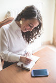 Beautiful woman at home writing and working — Stock Photo