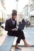 Stylish elegant dreadlocks businessman using notebook — Stock Photo