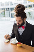 Stylish elegant dreadlocks businessman at the bar — Stock Photo