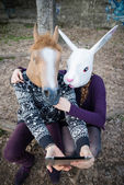 Young hipster cuople horse and rabbit mask using tablet — Stock Photo