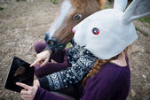 Young hipster cuople horse and rabbit mask using tablet — Foto Stock