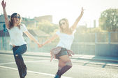 Two beautiful women jumping — Stock Photo