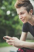 Young lesbian stylish hair style woman using smart phone — Stock Photo