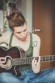 Young stylish woman playing guitar — Stock Photo