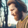 Young bearded stylish handsome hipster man listening music — Stock Photo #47679813