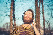 Young bearded stylish handsome hipster man listening music  — Stockfoto