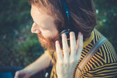 Young bearded stylish handsome hipster man listening music — Stock Photo
