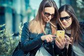 Two beautiful young women using smart phone — Stock Photo