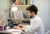 Handsome hipster modern man working home using laptop — Stock Photo