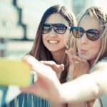 Two beautiful young women using smart phone selfie — Stock Photo #48321367