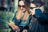 使用智能手机的两个漂亮的年轻女人 — 图库照片