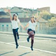 Two beautiful young women jumping and dancing — Stock Photo #49209583