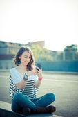 Junge schöne brünette frau mit smartphone — Stockfoto