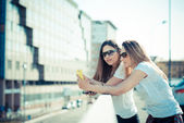 Two beautiful young women using smart phone — Stock Photo