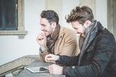 Dos jóvenes empresarios guapos usando la tableta — Foto de Stock