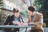 Two young handsome fashion model businessmen using tablet — Stock Photo