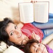 Mother and daughter smile while reading a book — Stock Photo