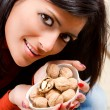 Young woman holds in her hand a little nuts — Stock Photo