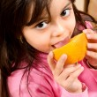 Little girl eating an orange — Stock Photo