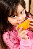 Little girl eating an orange — Stock Photo