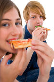 Couple of teenagers eating pizza — ストック写真