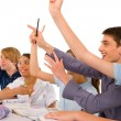 Teenagers in classroom with arms up — Stock Photo