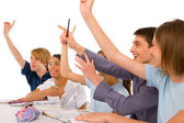 Teenagers in classroom with arms up — Stockfoto
