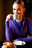 Woman drinking cappuccino at breakfast and looking at camera — Stock Photo