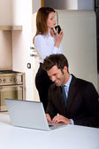 Couple at home with laptop and mobile — Foto de Stock