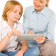Stock Photo: Mother and son sat on floor with tablet isolated on white backgr