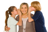 Young grandmother with nephew and niece standing on white backgr — Stock Photo