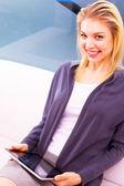 улыбаясь молодая женщина, держащая цифрового планшета — Стоковое фото