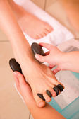 Woman receiving hot stone massage feet — Stock Photo