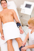 Man in beauty center having muscle mass check — Stock Photo