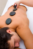Man having hot stone massage — Stock Photo