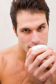 Man in spa holding cup near mouth — Stock Photo
