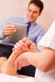 Masseuse massaging businessman's foot — Stock Photo