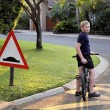 Stock Photo: Young Boy Stopped Bicycle at Speed Bump