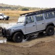 Постер, плакат: Silver Land Rover Defender 110 SW on 4x4 Course